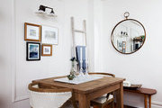 A porthole-style mirror in a minimalist dining area