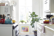 A kitchen with white walls, cabinetry, and countertops, plus colorful area rugs