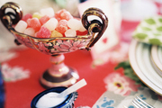 A dish of candy and a salt cellar atop a floral tablecloth