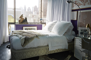 A bed draped with a hide and surrounded by artwork that can be concealed with drapery