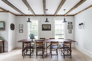 Industrial pendant lights hung above a wooden dining table and chairs