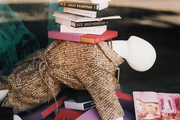 A stack of books atop a mannequin