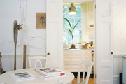 A white round dining table and chairs atop antique hardwoods