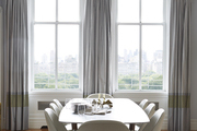 Tall grey drapes behind contemporary dining room table.