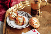 Apple-pear cider and goat cheese tarts on a gold tray with playing cards