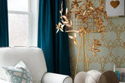 Patterned wallpaper and tall drapes in cozy children's room.