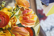A bouquet of ranunculus, tulips and freesia paired with Cotton & Flax trivets and Wolfum coasters