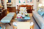 A pair of ottomans, floral-print chairs, and a roll-arm couch surrounding a glass coffee table