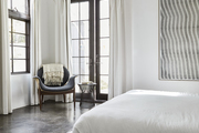 A gray bedroom with a low-profile bed and armchair with throw tossed over it,