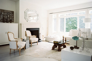 A pair of white armchairs in a neutral living room