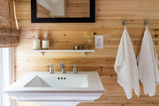 A country bathroom with pine plank-covered walls