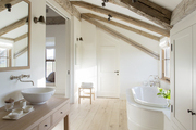Long bathroom with built in round tub and natural wood ceiling beams.