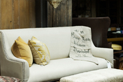 A white couch and an ottoman atop a cowhide rug