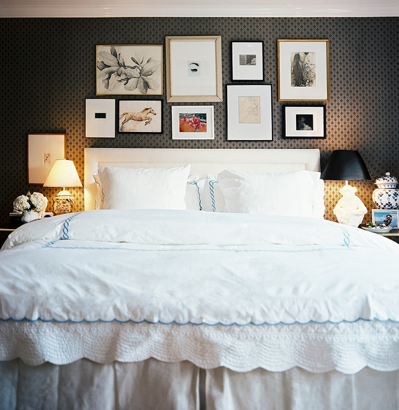 Ashley Putman - A grouping of art above an upholstered headboard paired with white scalloped bedding
