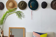 Hangnig hats, a color block throw pillow, a mirror, and a palm adorn this seating area.