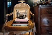 An antique chair topped with books beside a wooden chest