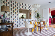 An eclectic dining space with striped wallpaper.