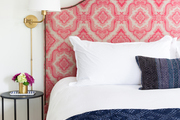 A contemporary bed with a pink-patterned headboard and indigo throw.