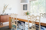 White Chinese Chippendale dining chairs and a wood table, accented by industrial lighting