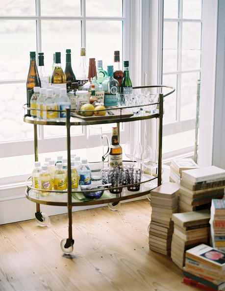 Bar Cart - A brass bar cart of spirits, mixers, and glassware