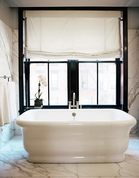 Bathroom - A white freestanding tub beside a window in a marble bathroom