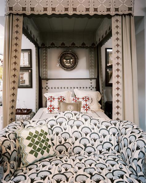 Bedroom Chair - A patterned settee at the foot of a canopy bed