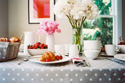 A Cath Kidston polka-dot tablecloth and vases filled with peonies decorate a country kitchen.