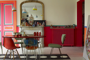 Mismatched chairs around a Paris dining table with a houndstooth rug on the wood floor