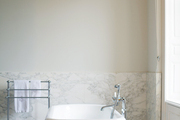 A clawfoot tub in a marble bathroom with a tiled floor