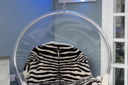 A hanging chair with a zebra print throw.