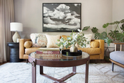 A contemporary living space with a metal coffee table and a tan couch.