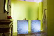 A bathroom with glowing panels of chartreuse glass, two marble sink stands, and original frescoed ceilings and terrazzo floors