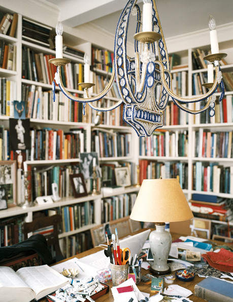 Book Shelves - A beaded chandelier above a wooden desk surrounded by books