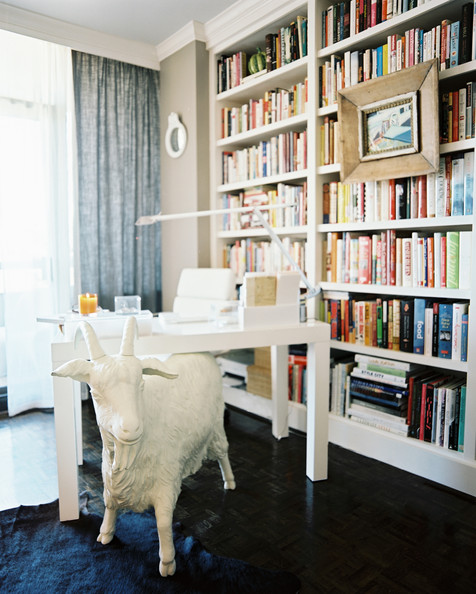 Bookshelf - A white goat statue in an office space with built-in bookshelves
