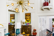 White walls framing a living space's Sputnik chandelier, upholstered bench and chair, and other eclectic decor