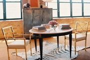 A pair of brass chairs and a round table atop a zebra hide rug