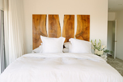 A combined bed with a unique wooden headboard.