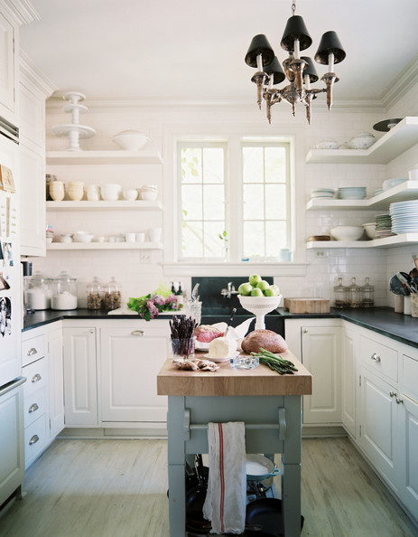 Butcher Block Island - A white kitchen with open shelving and black countertops