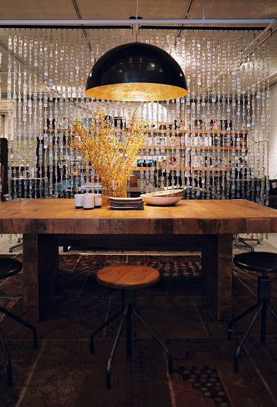 Butcher Block Table - A large black-and-gold light fixture above wooden stools and a rustic wooden table
