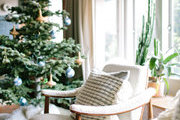 A decorated holiday tree next to a pair of white chairs.