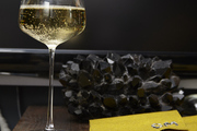 Large crystal wine glass and small tablecloths top a worn wood dresser.