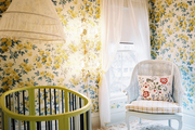 Yellow floral wallpaper and a green oval crib in a nursery