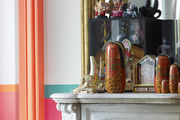 A vignette of objets on a mantel in front of a gold mirror in a Paris apartment