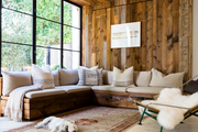 A sofa with beige cushions and patterned throw pillows; pine boards on the wall and ceiling