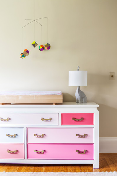 Chloe Warner - A geometric mobile above a dresser with drawers in shades of pink