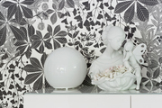 A detail of decorative items on a white credenza in front of gray and white wallpaper.