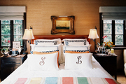 A striped throw and monogrammed linens on a wooden bed
