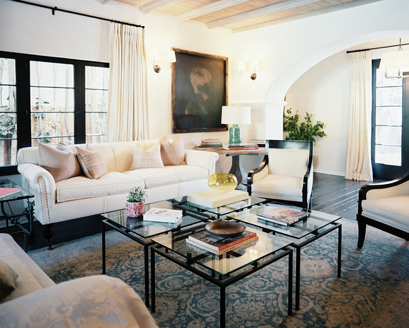 Coffee Table - A white sofa and pair of chairs with a grouping of four glass end tables
