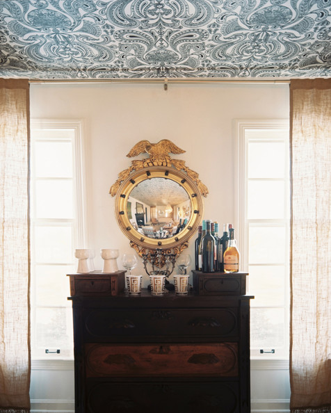 Convex Mirror - A wallpapered ceiling above a wooden chest and a gold convex mirror