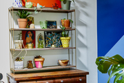 A wooden shelf holding many colorful pots and plants.